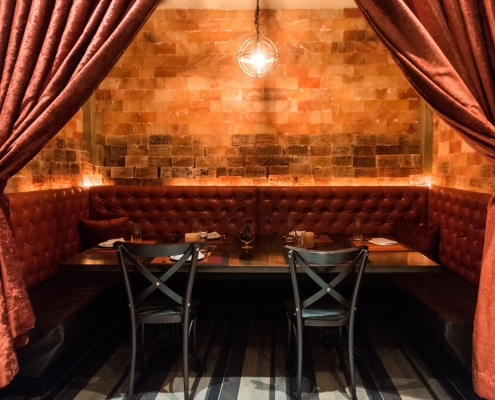 The Himalayan Pink Salt Room is a semi-private dining room with red curtains, banquettes and a large table, surrounded by pink salt bricks.
