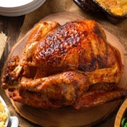 A Roasted Turkey is Pictured with sides, desserts and trimmings