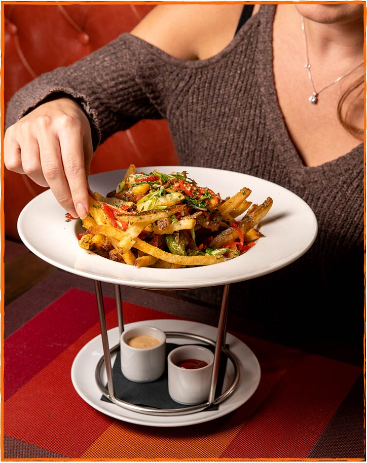 Picture of a woman eating hipster fries - available during happy hour