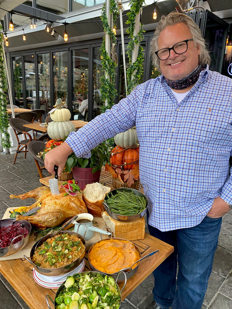 Chef David Burke standing next to a Turkey with all the traditional trimmings